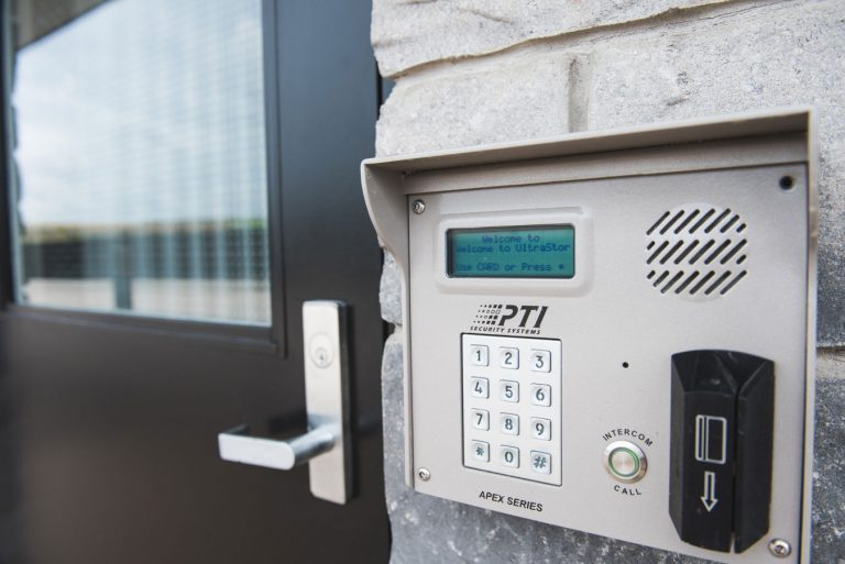 A black door with a secure UltraStor lock beside it, featuring key card access, code access and a speaker for added security.