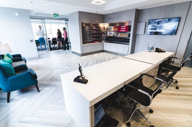 The entrance of UltraStor Burlington, just guest seating and client services desk and moving supplies for purchase.
