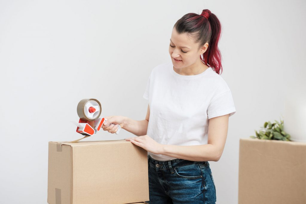 Person taping up a moving box with a tape roller, with another moving box waiting in the background.