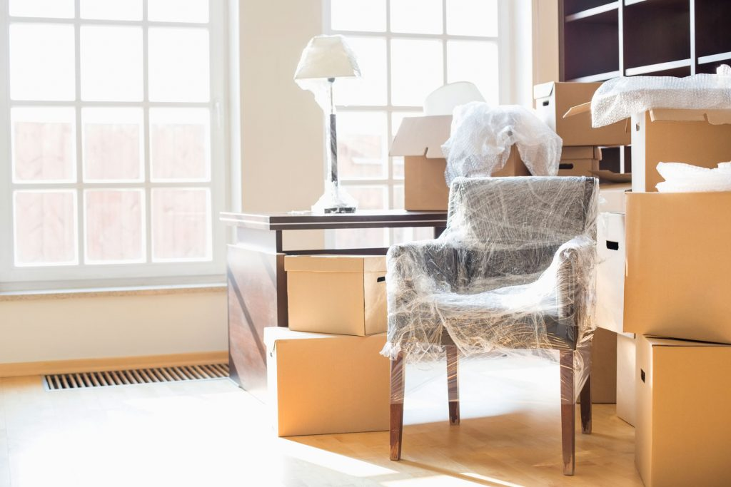 Moving boxes surround a bubble-wrapped chair and a table with a lamp.