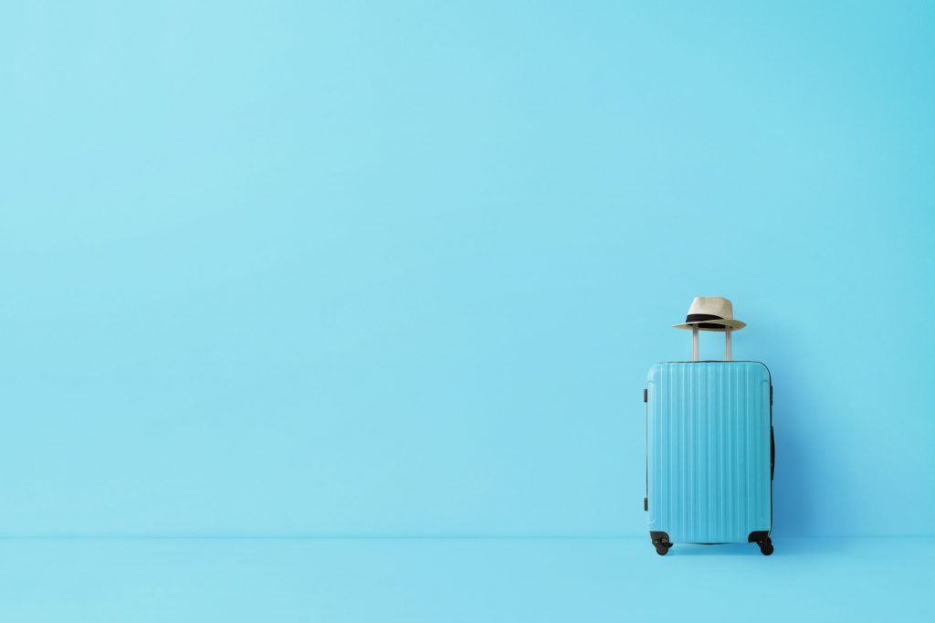 Blue, travelled-sized suitcase with a beige fedora on the handle, against a matching blue wall.