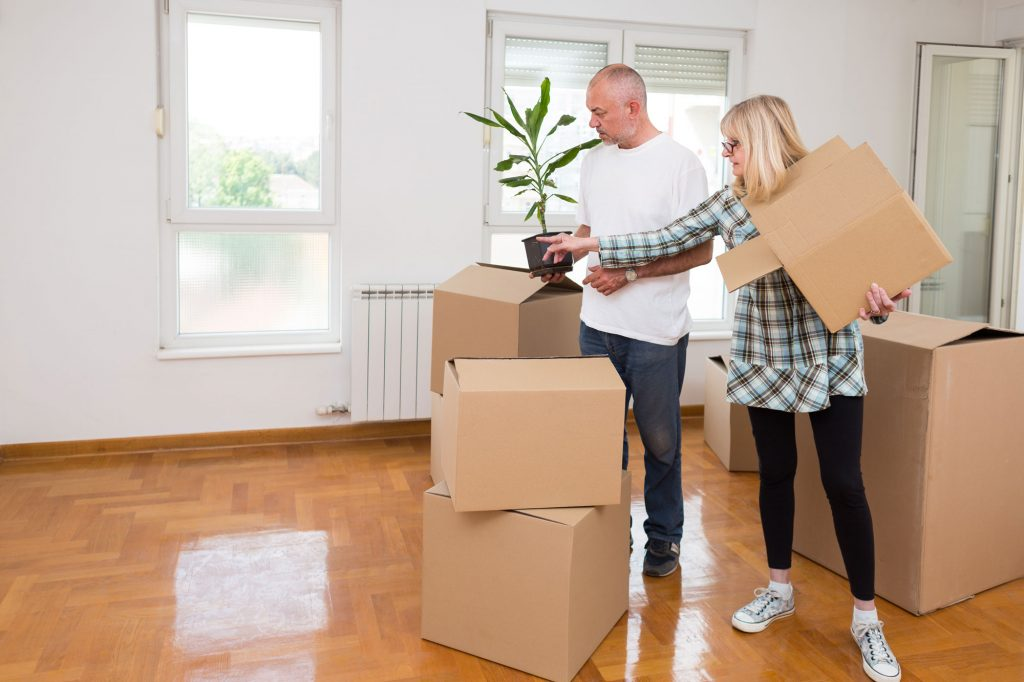 An older couple carrying a plant and packing up their belongings into boxes for UltraStor.