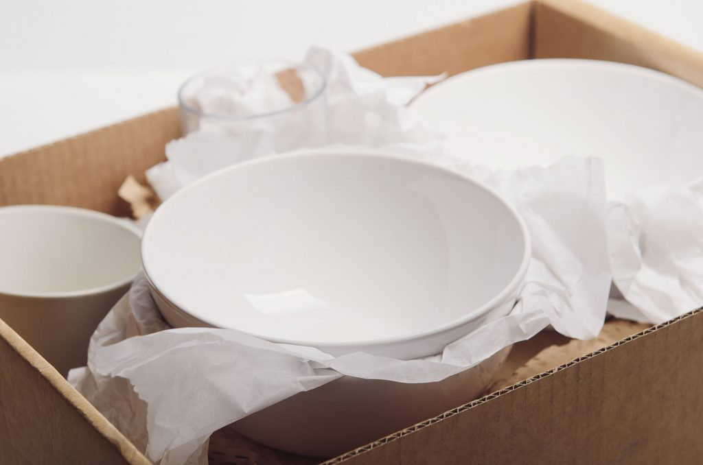 Open moving box filled with white tissue and white dishes in an UltraStor unit.