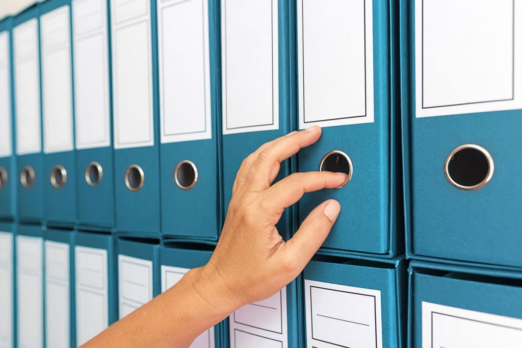 Rows of blue binders with a hand reaching to pull one out.