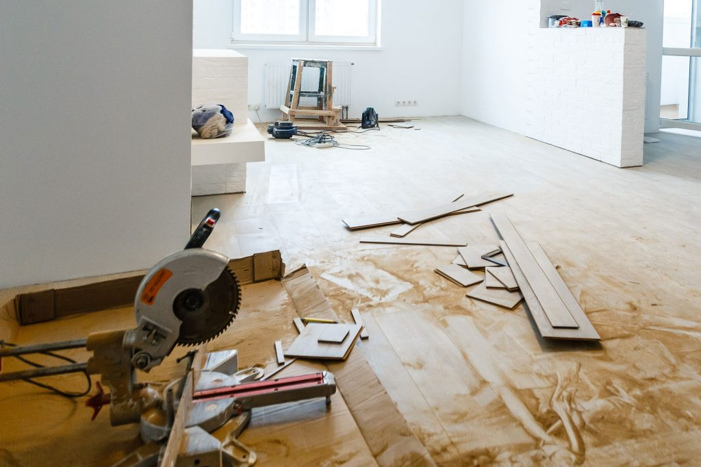 A home renovation underway, with various boards, a ladder and a table saw.