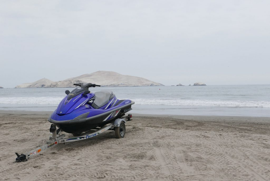 A jetski on a trailer, with a lake in the background on a foggy day.
