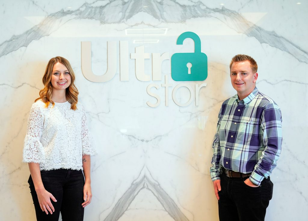 Members of the UltraStor team standing against the UltraStor logo.