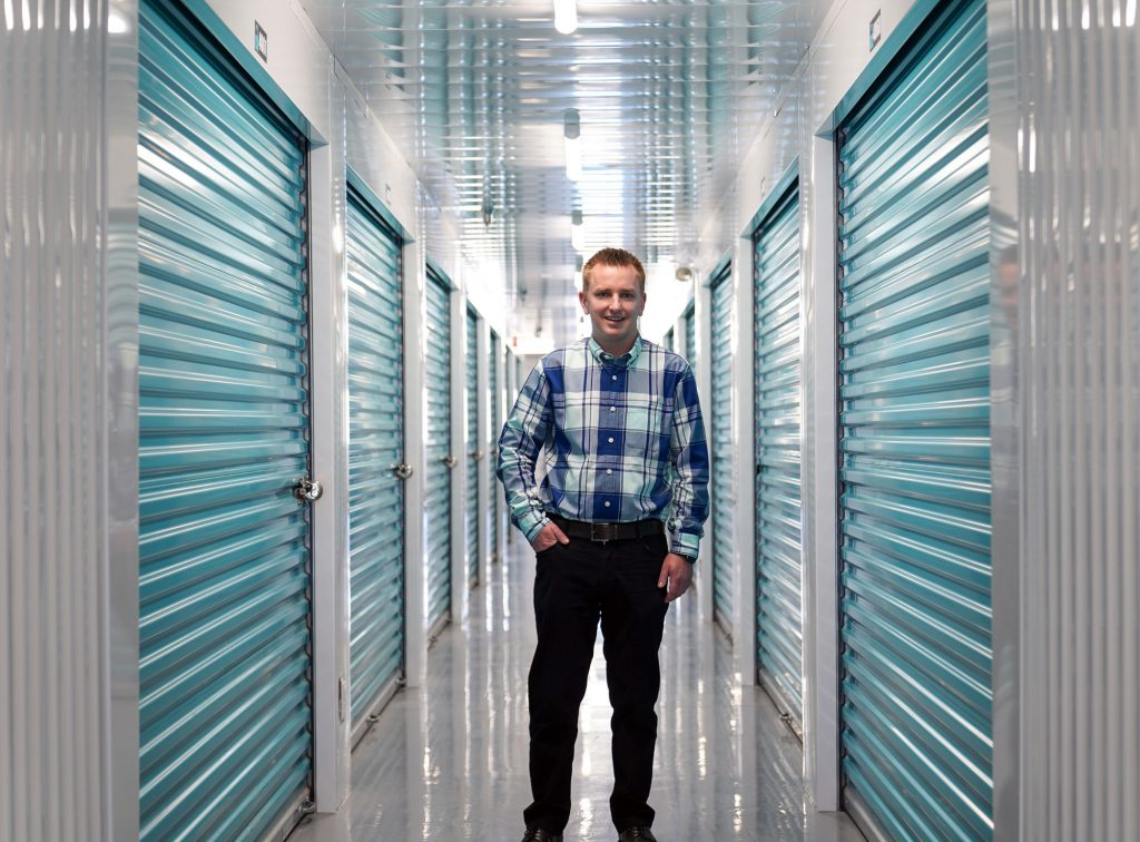 Member of the UltraStor team standing in a hallway of self-storage lockers.