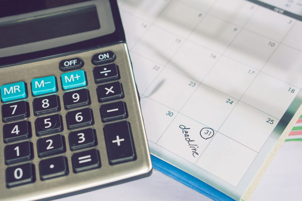 Calculator with a calendar in the background.